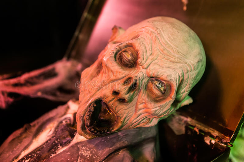 Horror mask peers out of coffin. In a haunted house royalty free stock photos