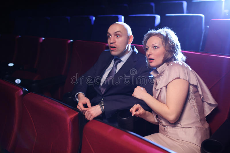 Horror movie. Couple in cinema movie theater scared watching horror film royalty free stock images
