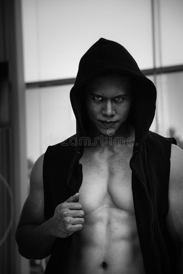 Horror muscular man wear black jacket with hood standing behind the window, black and white picture, stock photography