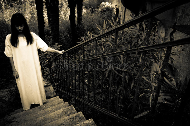 Horror scary woman. Female zombie on the stairs royalty free stock photos