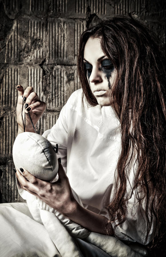 Horror scena: dziwaczna szalona dziewczyna z pacynki igłą w rękach i lalą fotografia royalty free