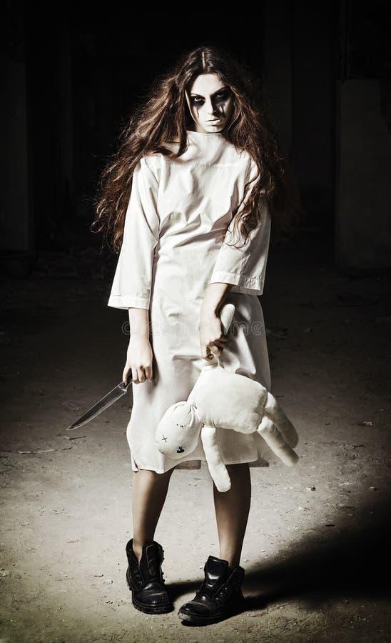 Horror scena: straszna potwór dziewczyna z pacynka nożem w rękach i lalą obrazy stock