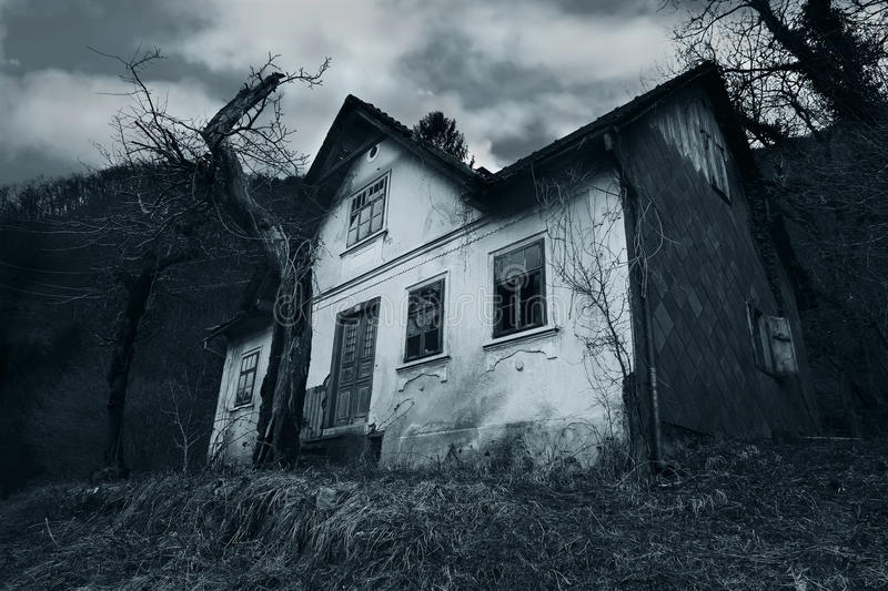 Horror scene of a abandoned house. Vintage horror house with blue filter stock photo