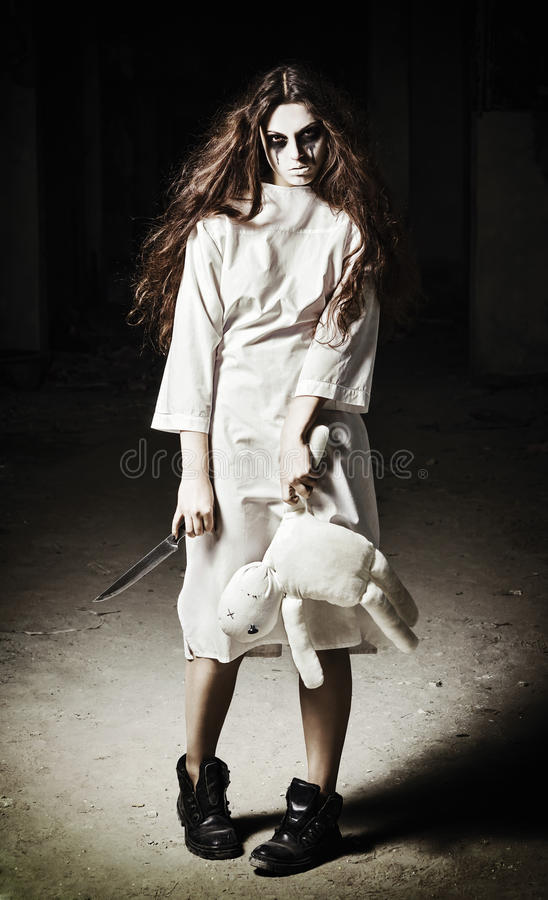 Horror scene: scary monster girl with moppet doll and knife in hands stock images
