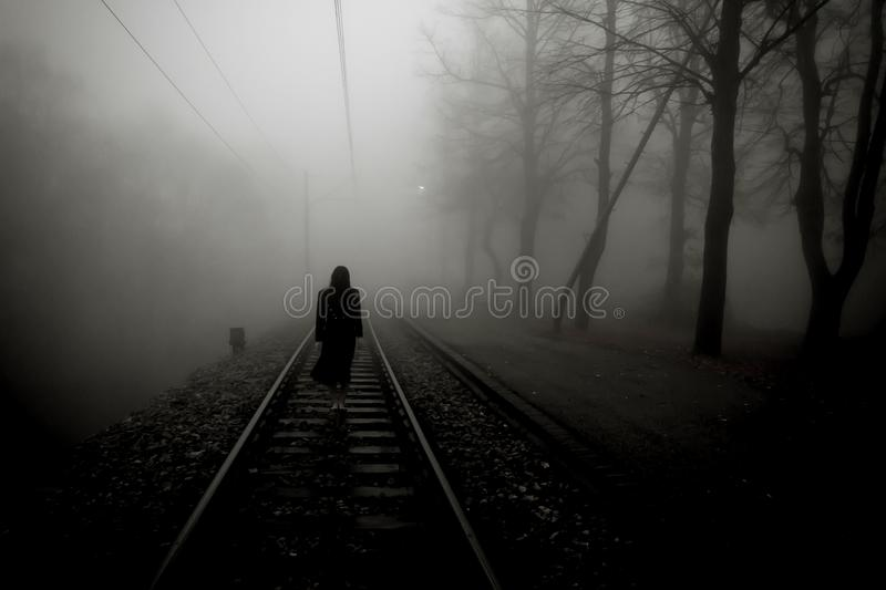 Horror scene of scary woman. Scary woman in black dress standing at the rails in the misty forest stock image