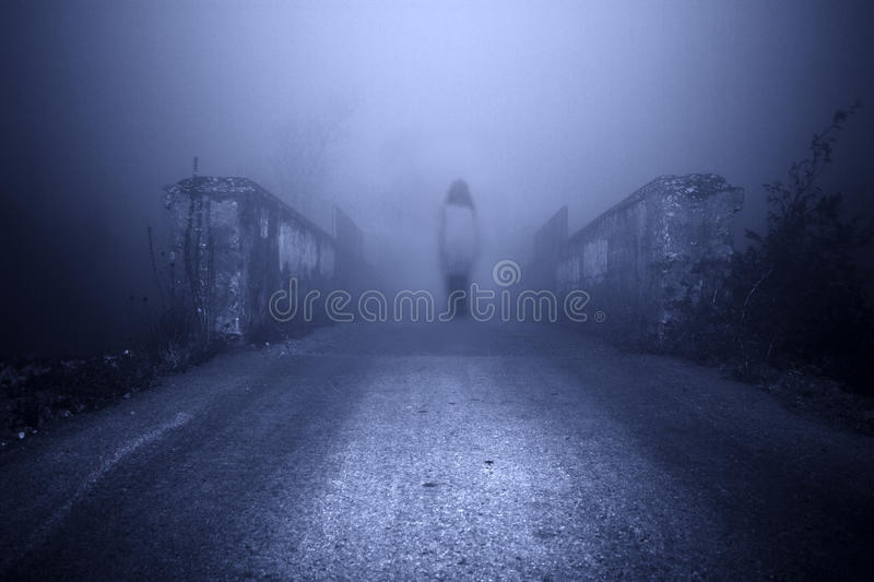 Horror scene of a scary woman. Haunted female ghost in the mist royalty free stock photos