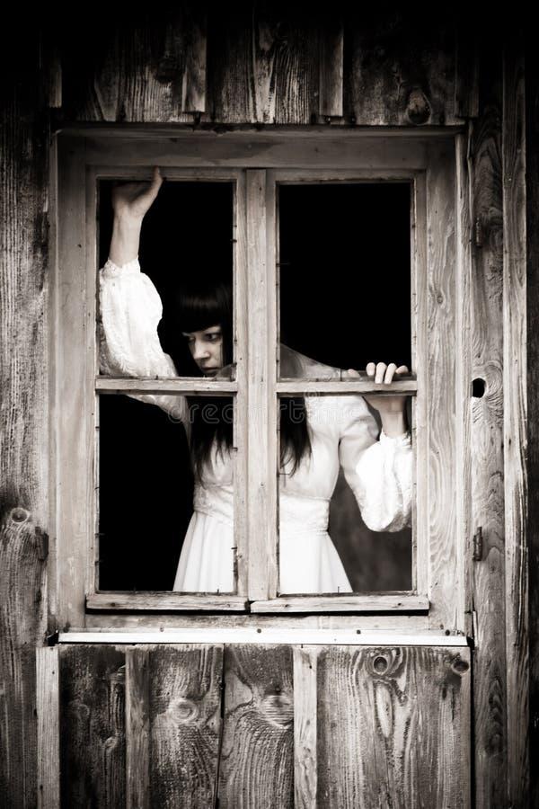Horror scene of a scary woman. The Horror scene of a scary woman. Woman stars out the old rustic window stock photos