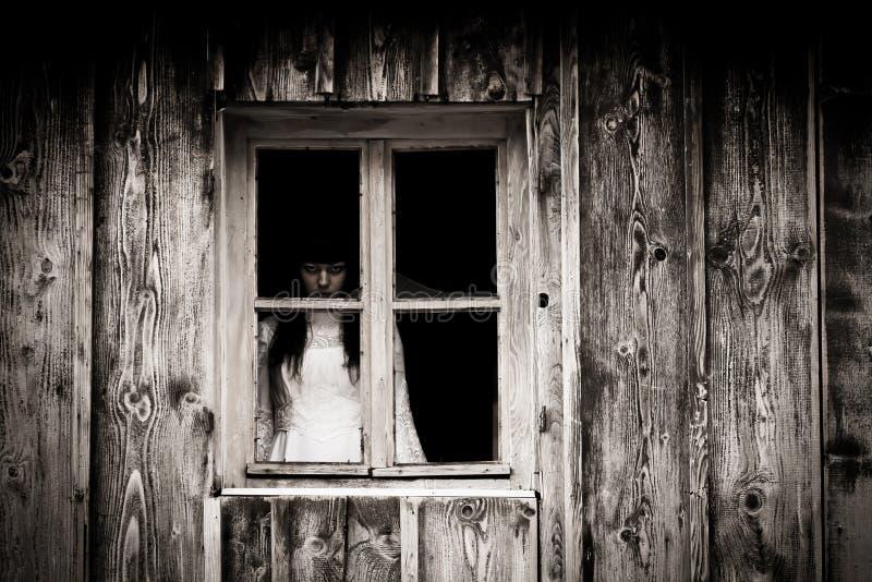 Horror scene of a scary woman. The Horror scene of a scary woman. Woman stars out the old rustic window royalty free stock photo