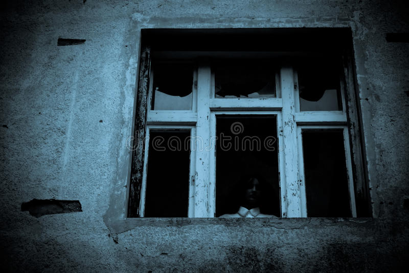 Horror scene. Scary woman at the window stock photo