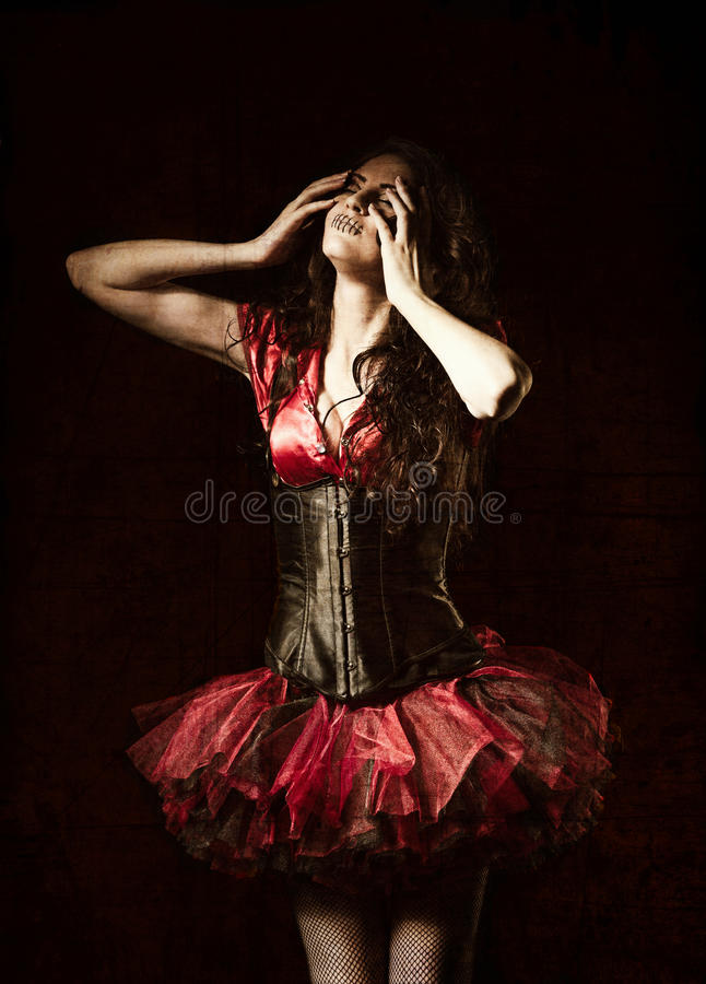 Horror shot: strange girl with mouth sewn shut among the dark. Grunge texture effect stock images