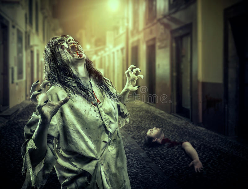 The horror shouting zombie girl on the dark street royalty free stock image