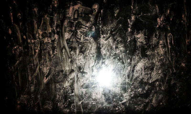 Horror silhouette behind the matte glass blood stain. Blurry hand and body figure abstraction. Background with fire. Selective focus royalty free stock images
