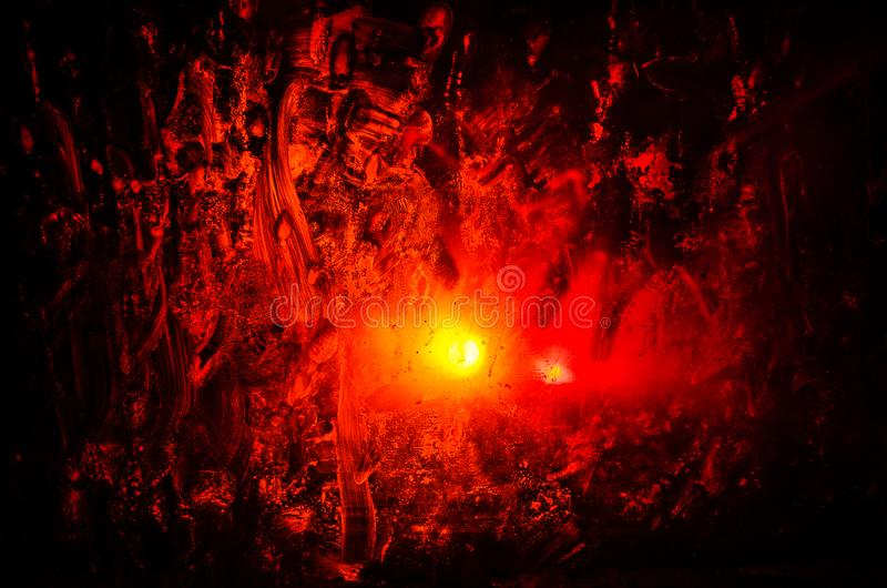 Horror silhouette behind the matte glass blood stain. Blurry hand and body figure abstraction. Background with fire. Selective focus royalty free stock image