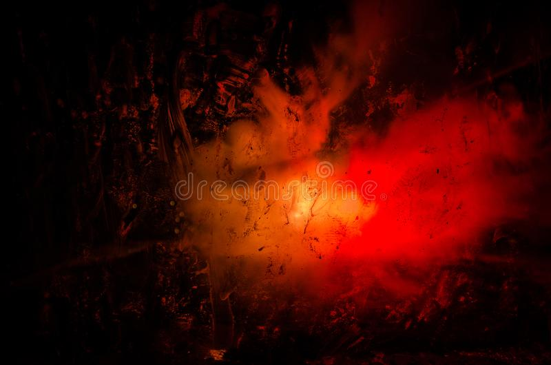 Horror silhouette behind the matte glass blood stain. Blurry hand and body figure abstraction. Background with fire. Selective focus stock photography
