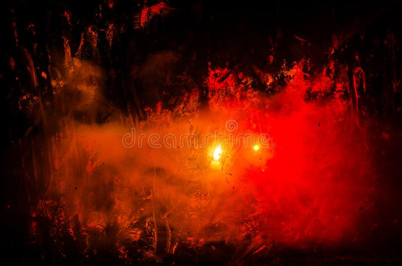 Horror silhouette behind the matte glass blood stain. Blurry hand and body figure abstraction. Background with fire. Selective focus stock image