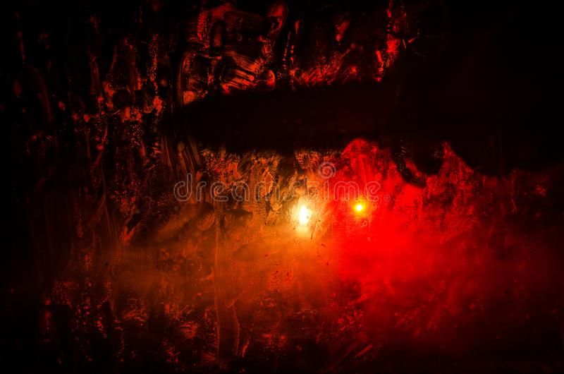 Horror silhouette behind the matte glass blood stain. Blurry hand and body figure abstraction. Background with fire. Selective focus stock photo