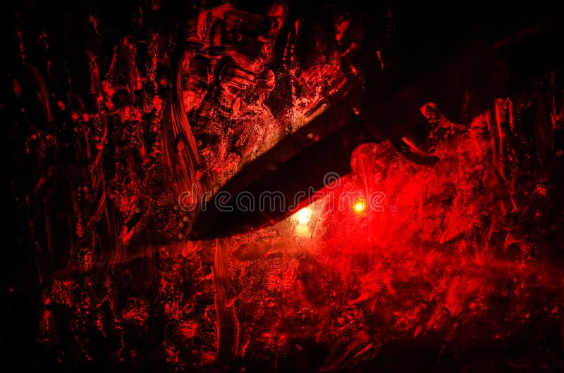 Horror silhouette behind the matte glass blood stain. Blurry hand and body figure abstraction. Background with fire. Selective focus royalty free stock photo