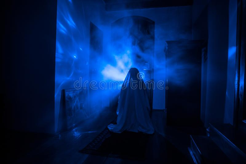 Horror silhouette of ghost inside dark room with mirror Scary halloween concept Silhouette of witch inside haunted house with fog royalty free stock photo