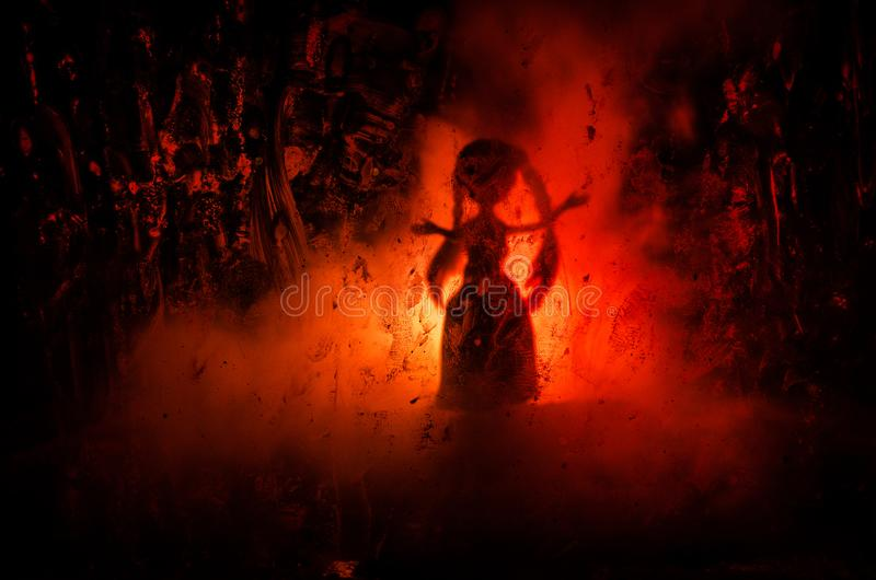 Horror silhouette of girl behind the matte glass blood stain. Blurry hand and body figure abstraction. Background with fire. Selective focus royalty free stock photography