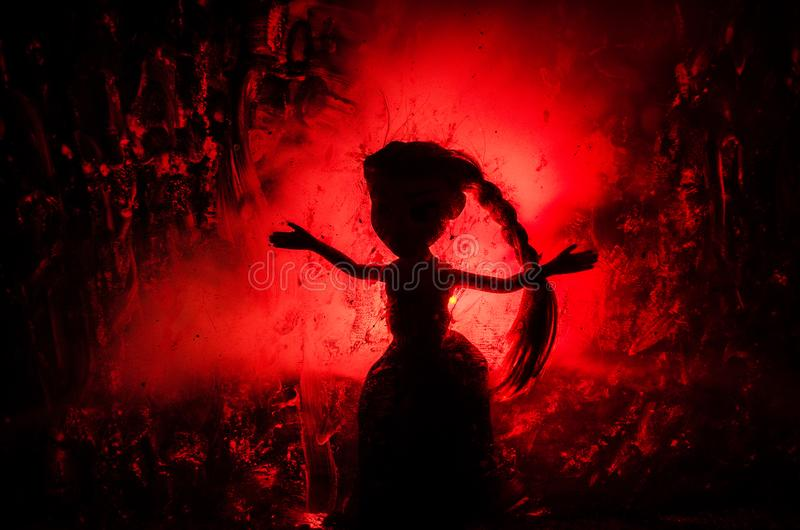 Horror silhouette of girl behind the matte glass blood stain. Blurry hand and body figure abstraction. Background with fire. Selective focus stock image