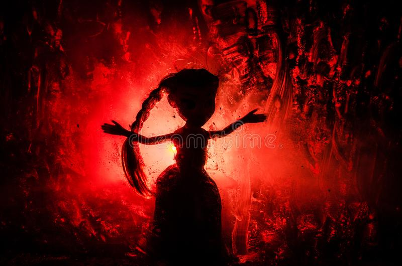 Horror silhouette of girl behind the matte glass blood stain. Blurry hand and body figure abstraction. Background with fire. Selective focus royalty free stock image