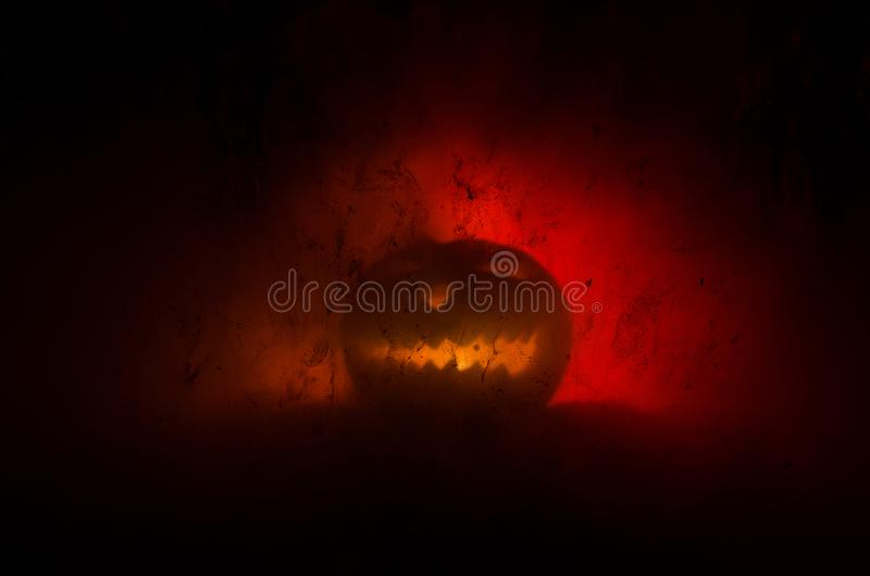 Horror silhouette of halloween pumkin behind the matte glass blood stain. Blurry hand and body figure abstraction. Background with royalty free stock photo