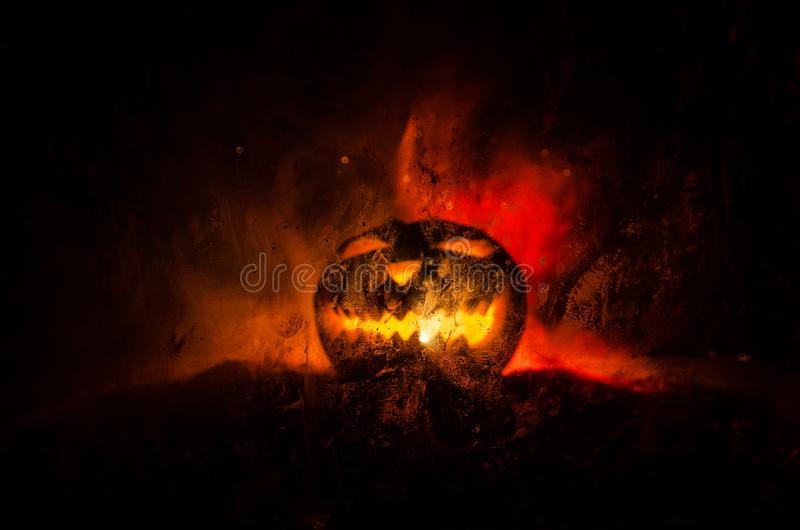 Horror silhouette of halloween pumkin behind the matte glass blood stain. Blurry hand and body figure abstraction. Background with. Fire. Selective focus stock photography