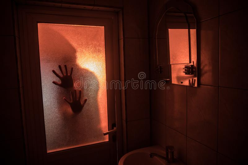Horror silhouette of woman in window. Scary halloween concept Blurred silhouette of witch in bathroom. Selective focus. Horror silhouette of woman in window royalty free stock photos