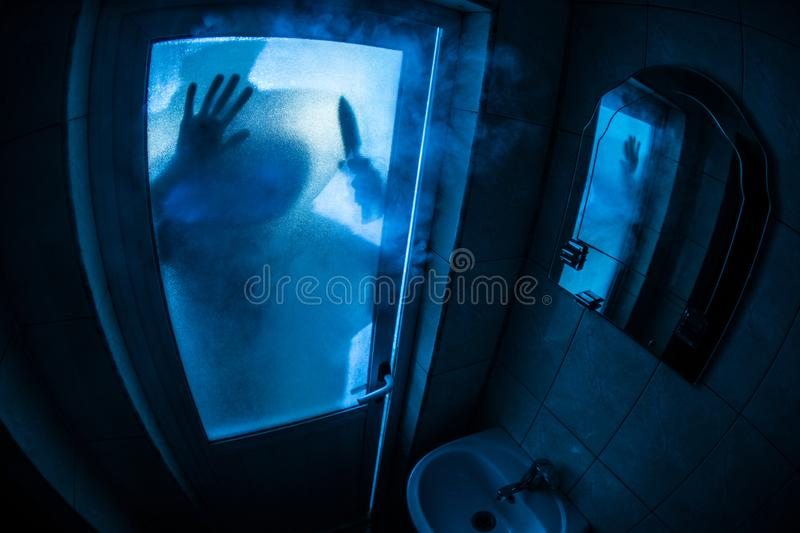 Horror silhouette of woman in window. Scary halloween concept Blurred silhouette of witch in bathroom. Selective focus. Horror silhouette of woman in window stock image