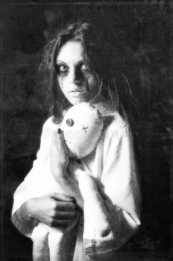 Horror style shot: mysterious ghost girl with moppet doll in hands. Grunge texture effect royalty free stock image
