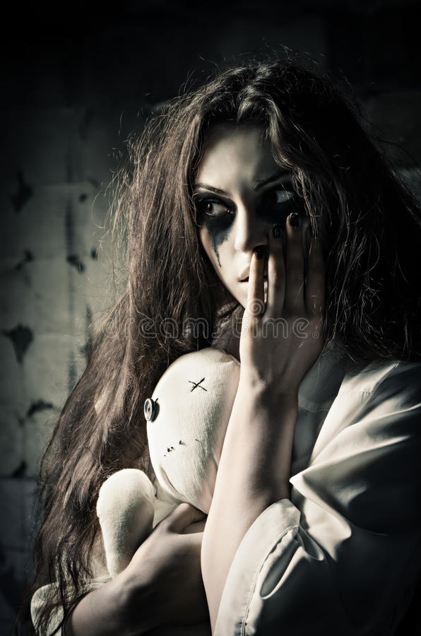 Horror style shot: strange sad girl with moppet doll in hands royalty free stock images