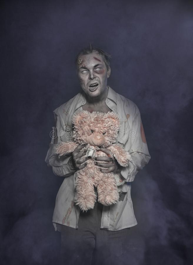 Horror terrible scary zombie man with teddy bear royalty free stock images