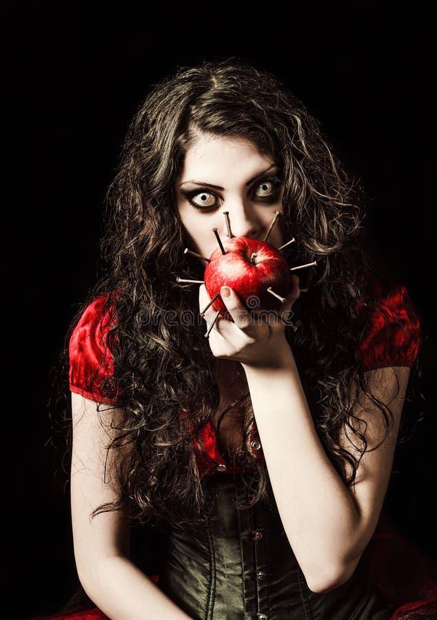 Horror tirado: la muchacha asustadiza extraña come la manzana tachonada con los clavos imagen de archivo