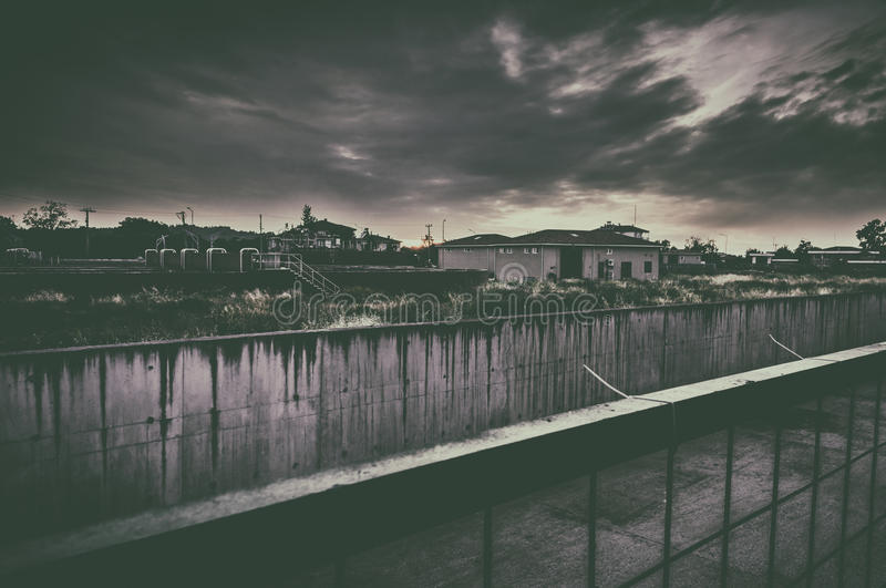 Horror Town Environment. Menacing dark clouds over a small town that feels desolated created a moody horror atmosphere with vintage look and muted color tones stock images