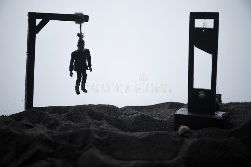 Horror view of hanged man on scaffold and Guillotine at misty evening with fog. Execution (or suicide) conceptual artwork royalty free stock photo