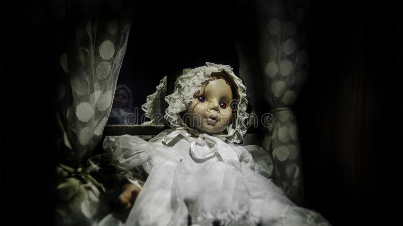 Horror vintage baby girl doll with scar face sit against the window, black vignette border effect for Halloween background stock images