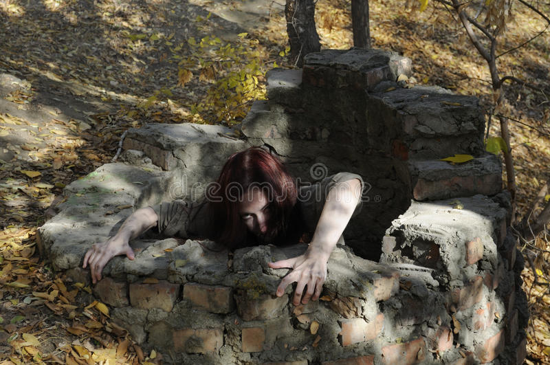 Horror woman. Crawling out of a brick well royalty free stock photos
