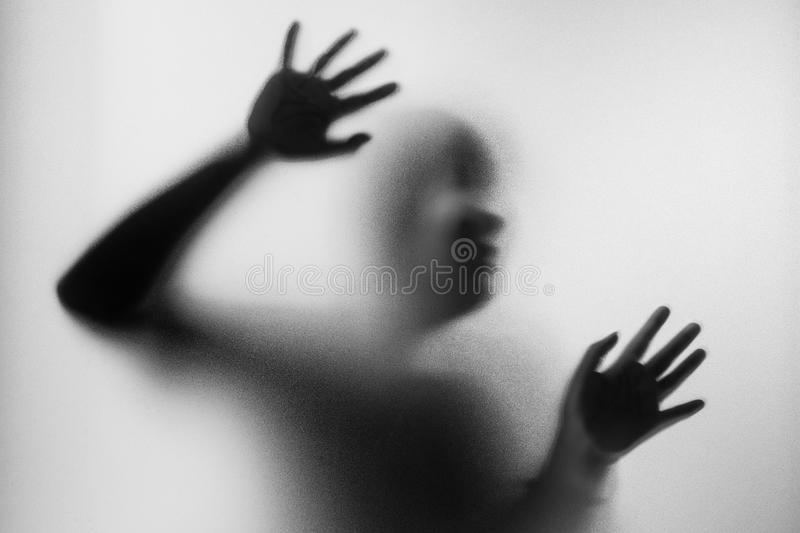 Horror woman behind the matte glass in black and white. Blurry h. And and body figure abstraction.Halloween background.Black and white picture stock photos
