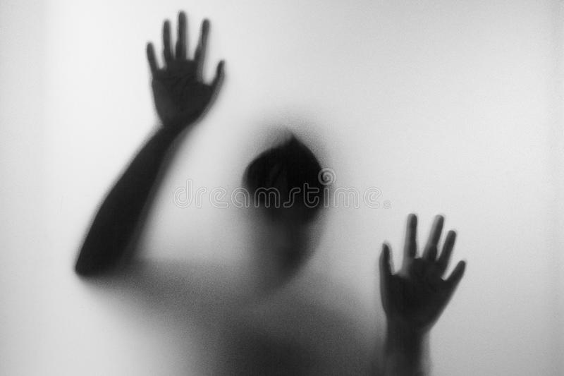 Horror woman behind the matte glass in black and white. Blurry hand and body figure abstraction.Halloween background.Black and stock photo