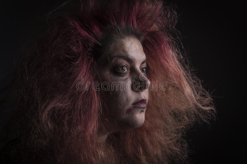Horror woman in the dark. Mad, deranged girl looking in the distance royalty free stock photo
