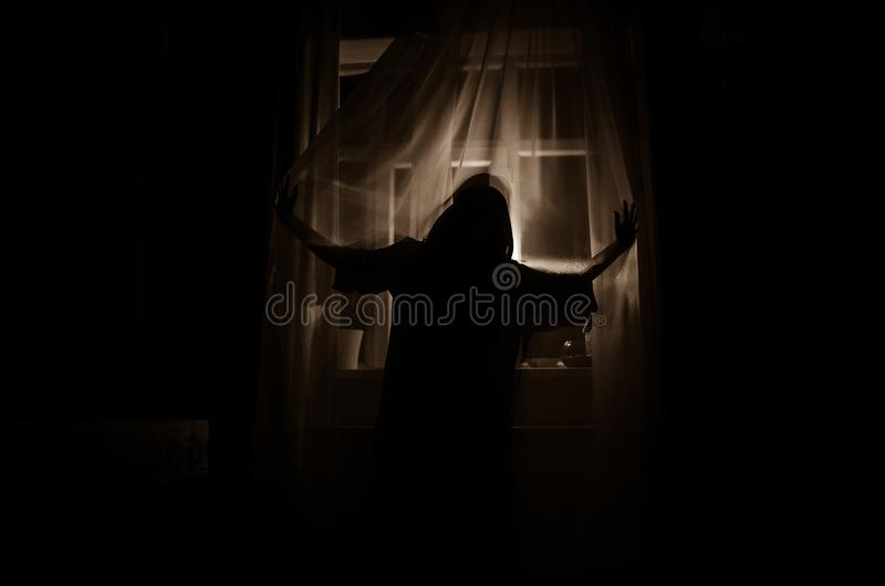 Horror woman in window wood hand hold cage scary scene halloween concept Blurred silhouette of witch. Selective focus. Horror woman in window wood hand hold cage royalty free stock photography