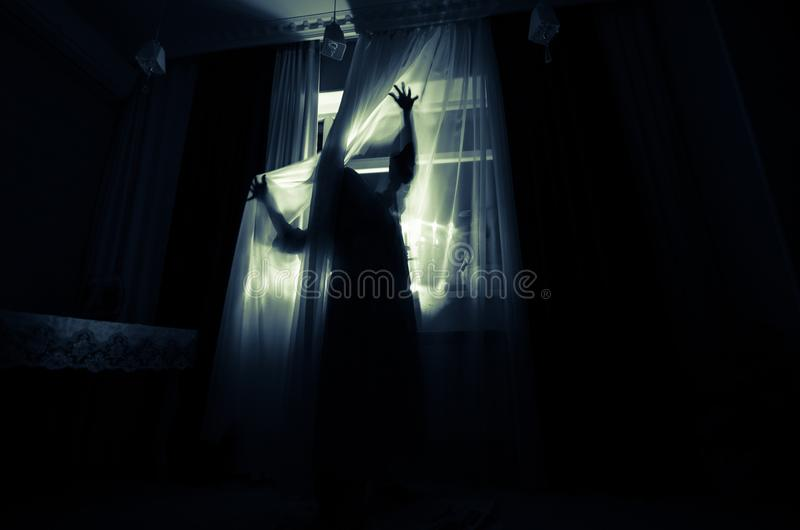 Horror woman in window wood hand hold cage scary scene halloween concept Blurred silhouette of witch. Selective focus. Horror woman in window wood hand hold cage royalty free stock image