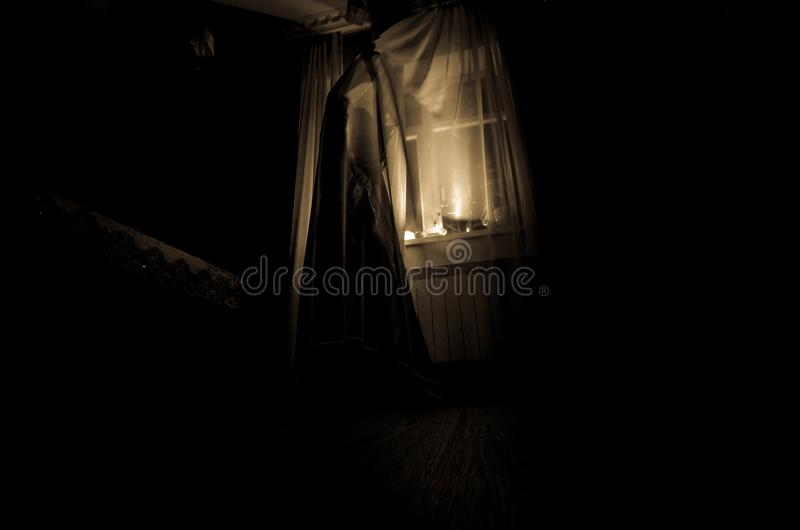 Horror woman in window wood hand hold cage scary scene halloween concept Blurred silhouette of witch. Selective focus. Horror woman in window wood hand hold cage stock images