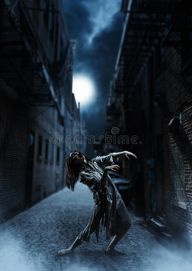 The horror zombie female on the dark street. Against the background of the moon. Halloween. Scary royalty free stock images