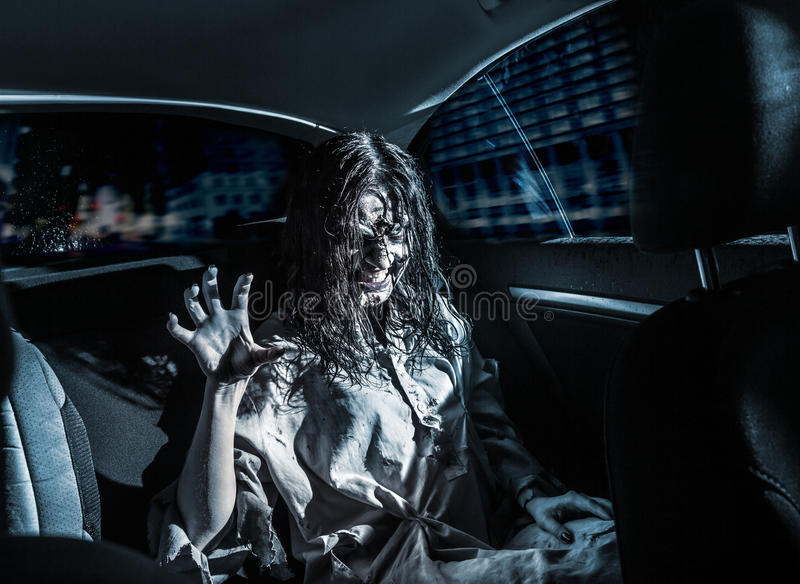 Horror zombie woman with bloody face in the car. The horror zombie woman with bloody face in the car, night city on the background. Scary. Halloween stock photos