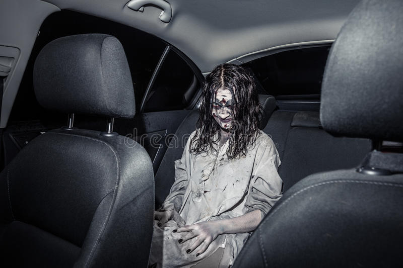 Horror zombie woman with bloody face in the car. The horror zombie woman with bloody face in the car, night city on the background. Scary. Halloween stock photo