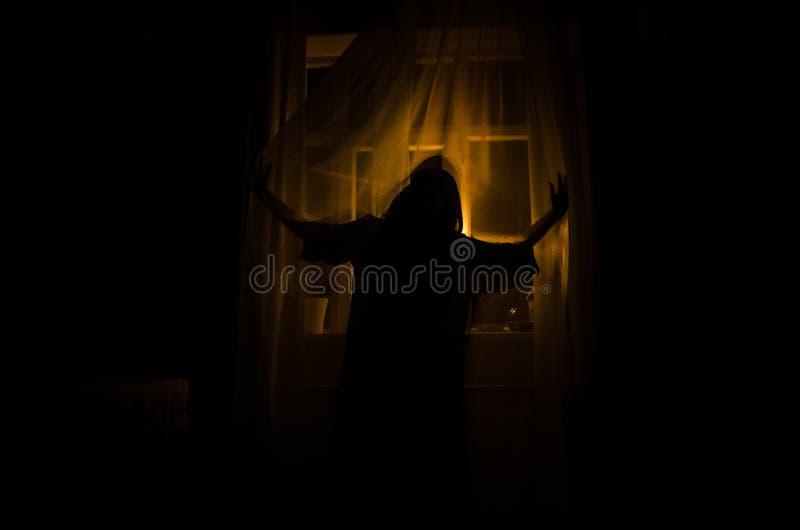 Horrorfrau in Griffkäfigs des Fensters Szenen-Halloween-Konzept des hölzernen Handfurchtsamem verwischte Schattenbild der Hexe Se stockfotos
