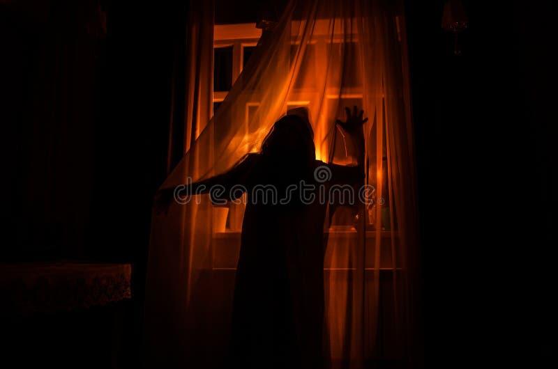 Horrorfrau in Griffkäfigs des Fensters Szenen-Halloween-Konzept des hölzernen Handfurchtsamem verwischte Schattenbild der Hexe Se stockbild