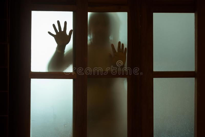 Horrorfrau hinter dem Fensterglas in Schwarzweiss blurry lizenzfreie stockfotografie