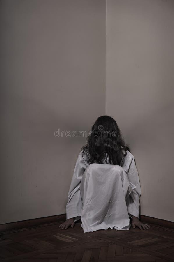 Horrorful-Mädchen, das an der Ecke sitzt lizenzfreie stockfotografie
